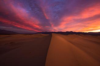 "A fiery sunrise over the Mesquite Sand Dunes in Death Valley National Park in California. Many first time visitors to Death Valley are surprised it is not covered with a sea of sand. Less than one percent of the desert is covered with dunes, yet the shadowed ripples and stark, graceful curves define ""desert"" in our imaginations. The Mesquite Flat Dunes are the best known and easiest to visit in the national park. Photo by Mike Mezeul II. Tweeted by the US Department of the Interior, 4/24/15."