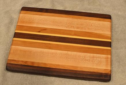 "Cheese Board # 15 - 065. Black Walnut, Cherry, Hard Maple & Yellowheart. 8"" x 11"" x 3/4""."