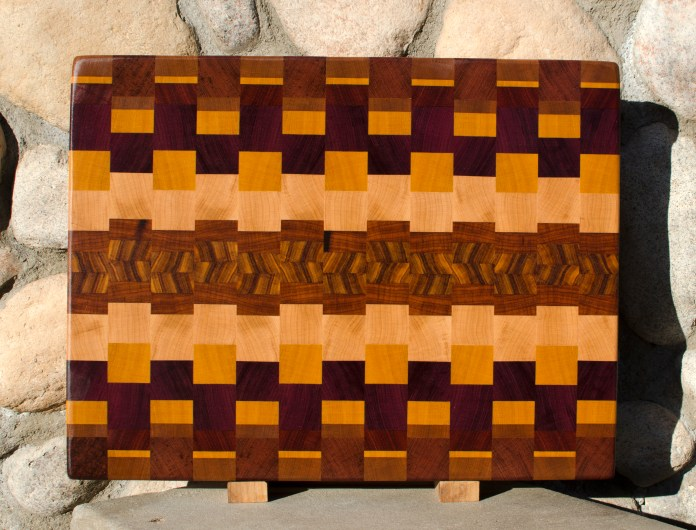 "Cutting Board 16 - End 040. Bubinga, Cherry, Bloodwood, Goncalo Alves, Canarywood, Padauk, Purpleheart, Yellowheart & Hard Maple. 16"" x 21"" x 1-1/2""."