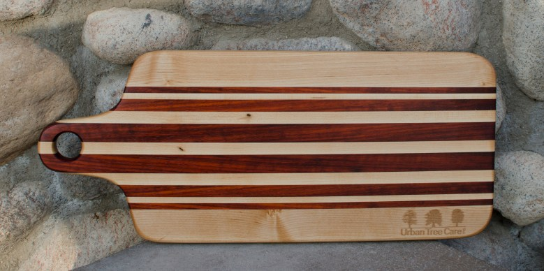 """Engraved 16 - 56. Bread board made for Urban Tree Care. Hard Maple and Bloodwood. 8"""" x 20"""" x 1""""."""