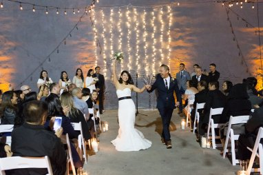 Wedding ceremony. Bride and Groom just married walking up the aisle. White string lights backdrop. Moxie Bright Events.