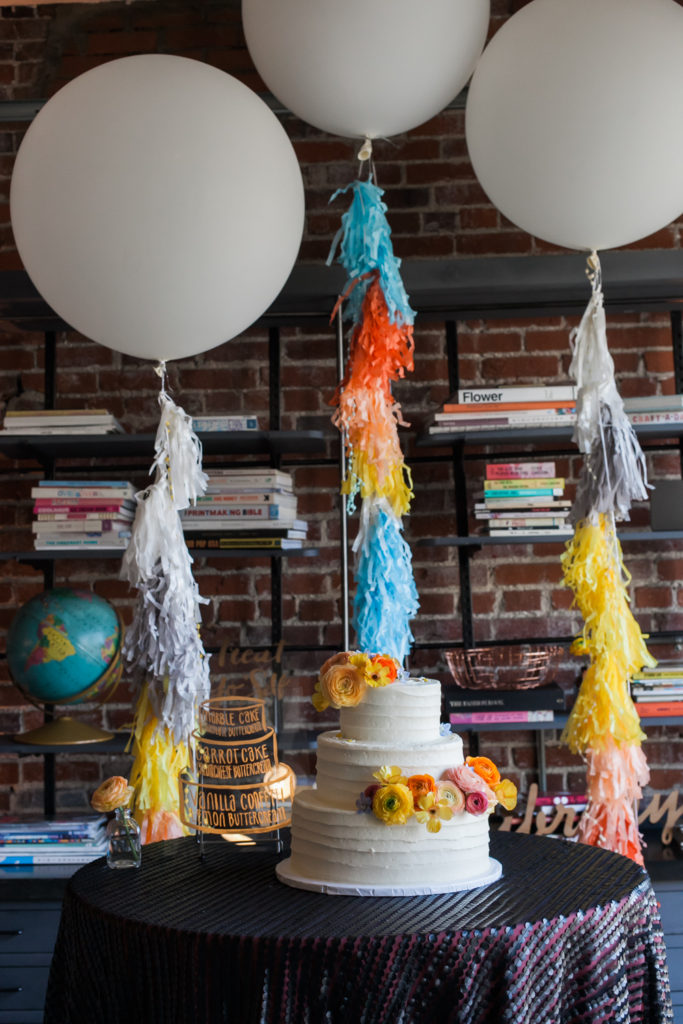 Three-tiered white wedding cake with balloons