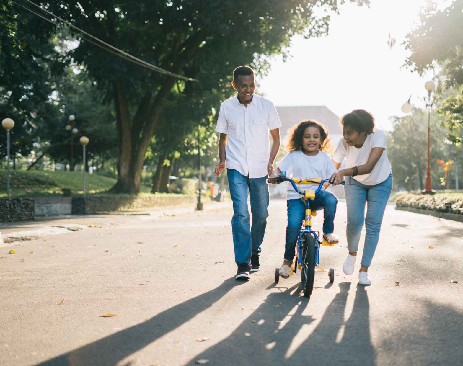 Man standing beside his wife teaching their child how to ride bicycle to Help their kid Deal with Stress During the Pandemic.