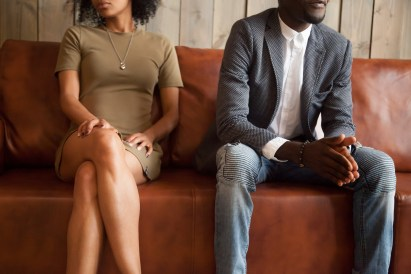 A couple face away from one another as they sit on a couch. They're trying to work through their differences with marriage counseling in Orange County, CA. Moxie Family Counseling offers couples therapy, relationship counseling, and more. Contact us for online marriage counseling, and more.