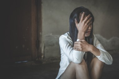 Woman sits with her hand on her face as she appears depressed. This symbolizes the pain and isolation that comes from past trauma. Moxie Family Therapy offers trauma therapy in Orange County, CA, ptsd treatment, emdr therapy for trauma, and more.