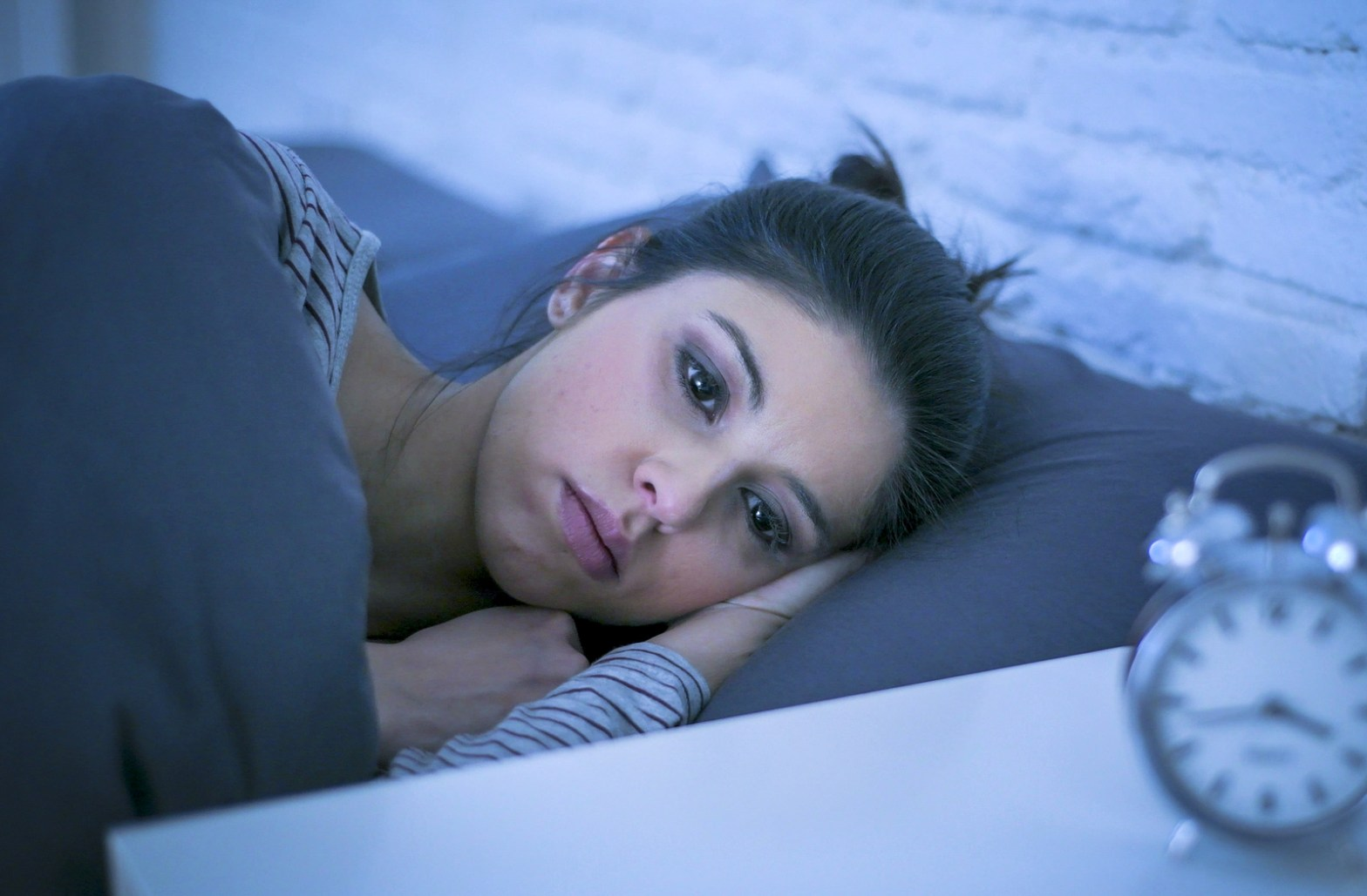 A woman with a blank stare lays in bed. This could represent anxiety related insomnia. Anxiety treatment in Orange County, CA can provide support. Contact an anxiety therapist to learn more about anxiety treatment for teens in Orange County, CA.