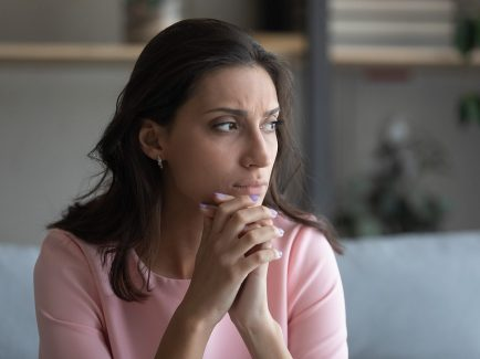 A concerned woman sits with her hands together as she looks off into the distance. This could represent he loneliness felt as a result of remembering a past traumatic event. Contact a trauma therapist in Orange County, CA for support with trauma therapy in Santa Ana, CA, and across the state! Orange County trauma treatment can provide the support you deserve!