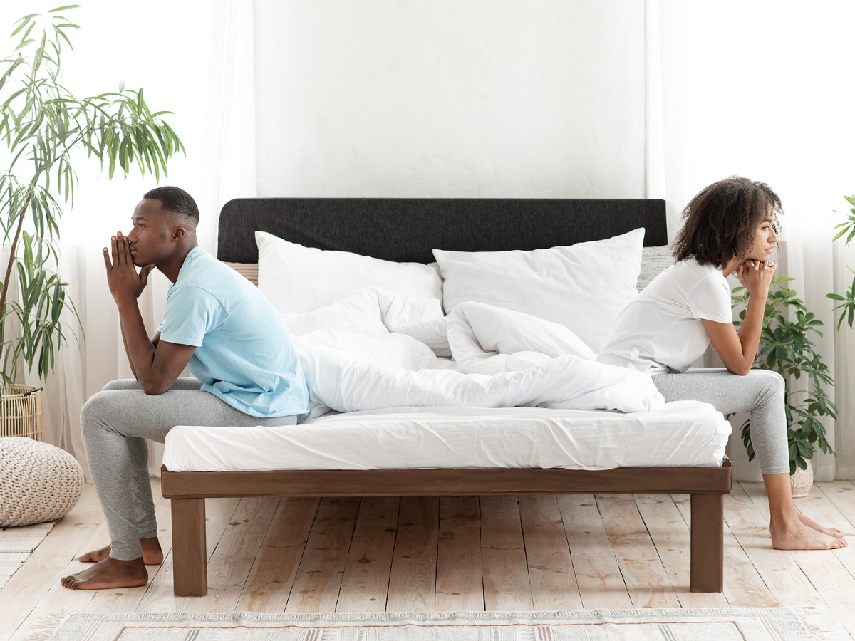 A couple ignore one another by sitting on either side of their bed. This could represent a couple that needs codependency therapy in Orange County, CA. Contact an online therapist today for more info on counseling for women in Orange County, CA!