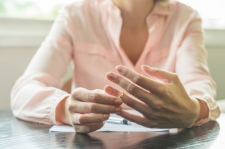 A woman pulls at her wedding band as a paper and pen lay in front of her. Counseling for women in Orange County, CA can support you through divorce. Contact a trauma therapist to learn how trauma therapy in Orange County, CA can support you in coping with divorce. 92701 | 92805 | 92704