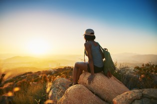 An image of a woman sits on rock on top of hill while looking at sunset for Moxie Family Therapy. Learn how trauma therapy in Orange County, CA can help you overcome break up trauma today. A trauma therapist can provide online therapy for trauma and other services. 92701 | 92683 | 92886