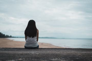 A woman sits alone as she looks out at the receding tide. A relationship therapist in Orange County, CA can help you combat loneliness. Learn more about therapy for loneliness at Moxie Family Therapy today. 92701 | 92805 | 92806