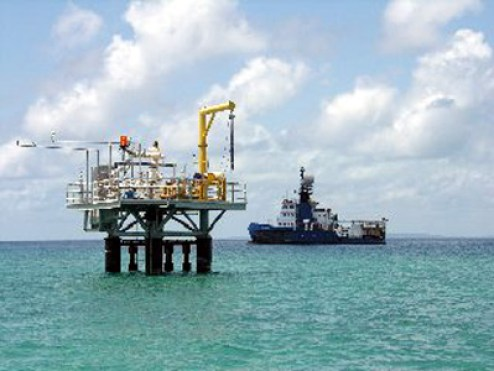 One of the producing Songo Songo gas wells, with Orca Exploration seismic programme survey vessel Geomariner in background.