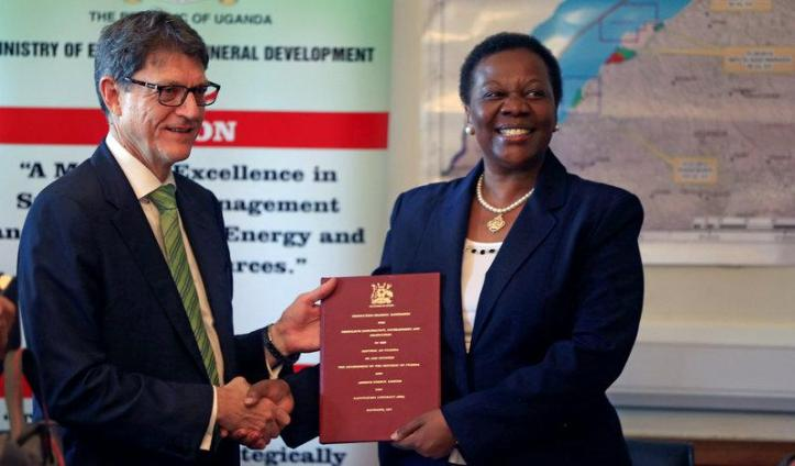 Uganda's Minister for Energy and Mineral Development, Irene Muloni (R), poses for a picture with Roger Cressey, CEO of Armour Energy, after signing a Production Sharing Agreement (PSA), in Kampala