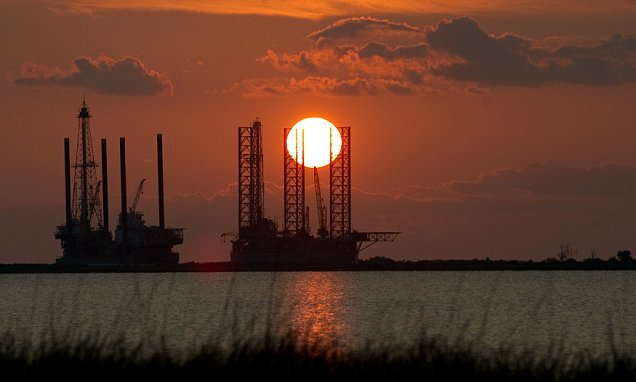 The sun sets behind two under constructi