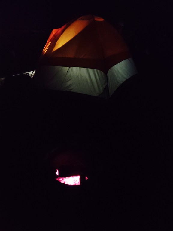 Photo of a campfire and a tent at night. The orange and grey tent is illuminated from the inside by a flashlight.