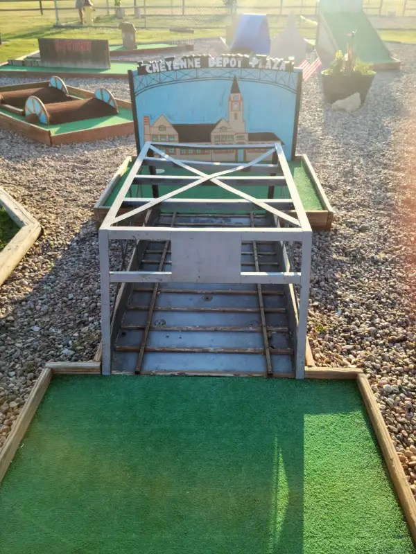 Cheyenne Depot Plaza mini golf. A hole with green turf, a wood miniature rail road bridge, and a sign that reads Cheyenne Depot Plaza.