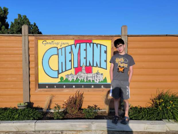 Buddy in grey stands in front of a brown wall with a yellow, blue, and red Greetings from Cheyenne, WY mural.