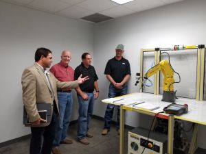 Man pointing to robotic arm in front of three other men