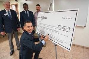Man signing large check