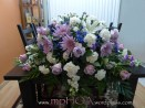 # MPCASK001 — $285.00 — Lavender Roses, Lavender Spider Mums, White Oriental Lilies, White Stocks, White Carnations, White Mini Carnations, Lavender Mini Carnations, Blue Delphiniums. ~ Approximate size: 18″H x 38″W. ~