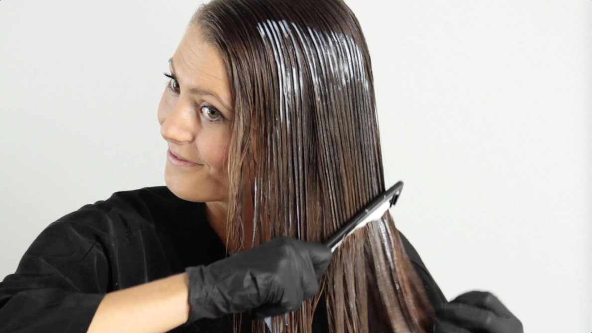woman with brown hair applying hair toner