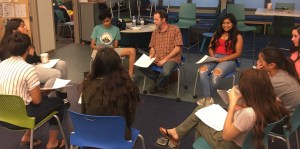 Students sitting in a circle with a male instructor.