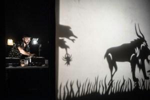 A puppet artist arranges a scene from behind a screen
