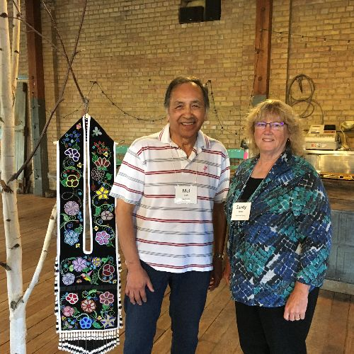 Anishinaabe Arts Intiative grantee and master bead and porcupine quill worker Mel Losh (Leech Lake Ojibwe) with former Region 2 Arts Council board chair Sandy Roman. Next to Mel is his beaded bandolier bag.