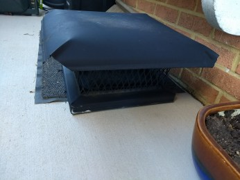 large black metal chimney cap sitting on concrete porch