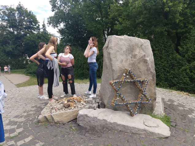 Abby Scheinberg explains part of what she read in Hebrew on the memorial