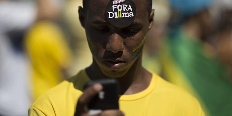 "A man holds his cellphone wearing a sticker in his forehead that reads in Portuguese ""Dilma out"" during a protest demanding the impeachment of Brazil's President Dilma Rousseff in Rio de Janeiro, Brazil, Sunday, Aug. 16, 2015. Demonstrators are taking to the streets across Brazil for a day of nationwide anti-government protests. President Rousseff's second term in office has been shaken by a snowballing corruption scandal involving politicians from her Workers' Party, as well as a spluttering economy, spiraling currency and rising inflation, making her popularity ratings fall to historic lows. (AP Photo/Leo Correa)"