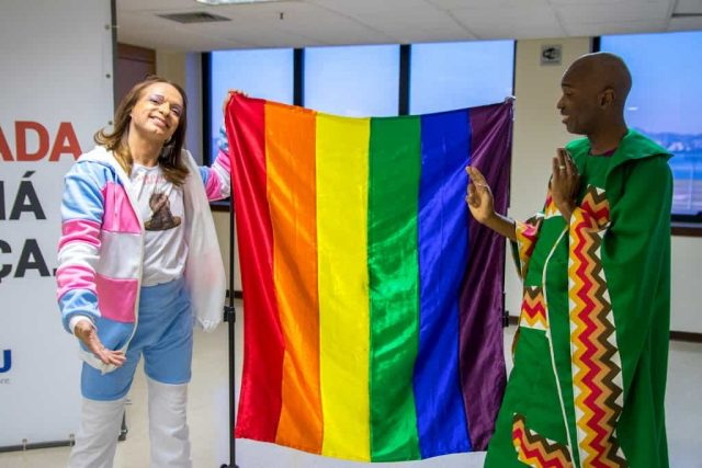 Students holding the rainbow flag in the graduation's fashion show