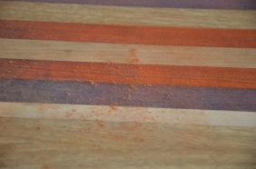 As you sand the board, the oil-inundated wood fibers on the surface must be removed to get to the raw wood underneath.