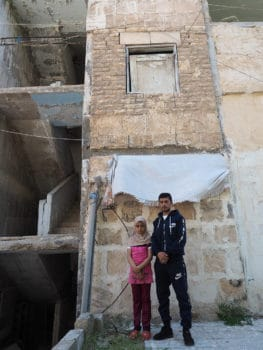 Mohamed and his sister Asma outside their Aleppo apartment block