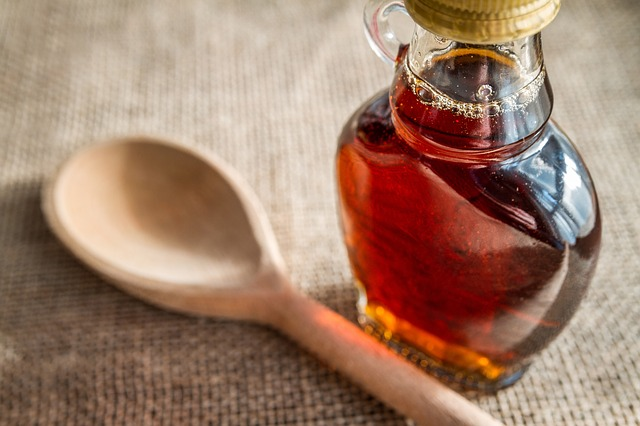 Bottle of maple syrup and spoon