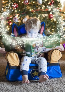 photograph of a small child reading a book surrounded by sparkles and light