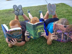 photograph of 2 boys and a girl lying on some grass, reading books
