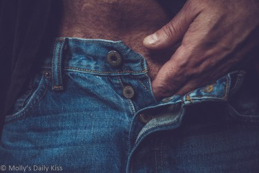 man's hand moving down the front of un-buttoned jeans
