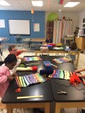 4th grade adding yarn tassels to their line paintings.