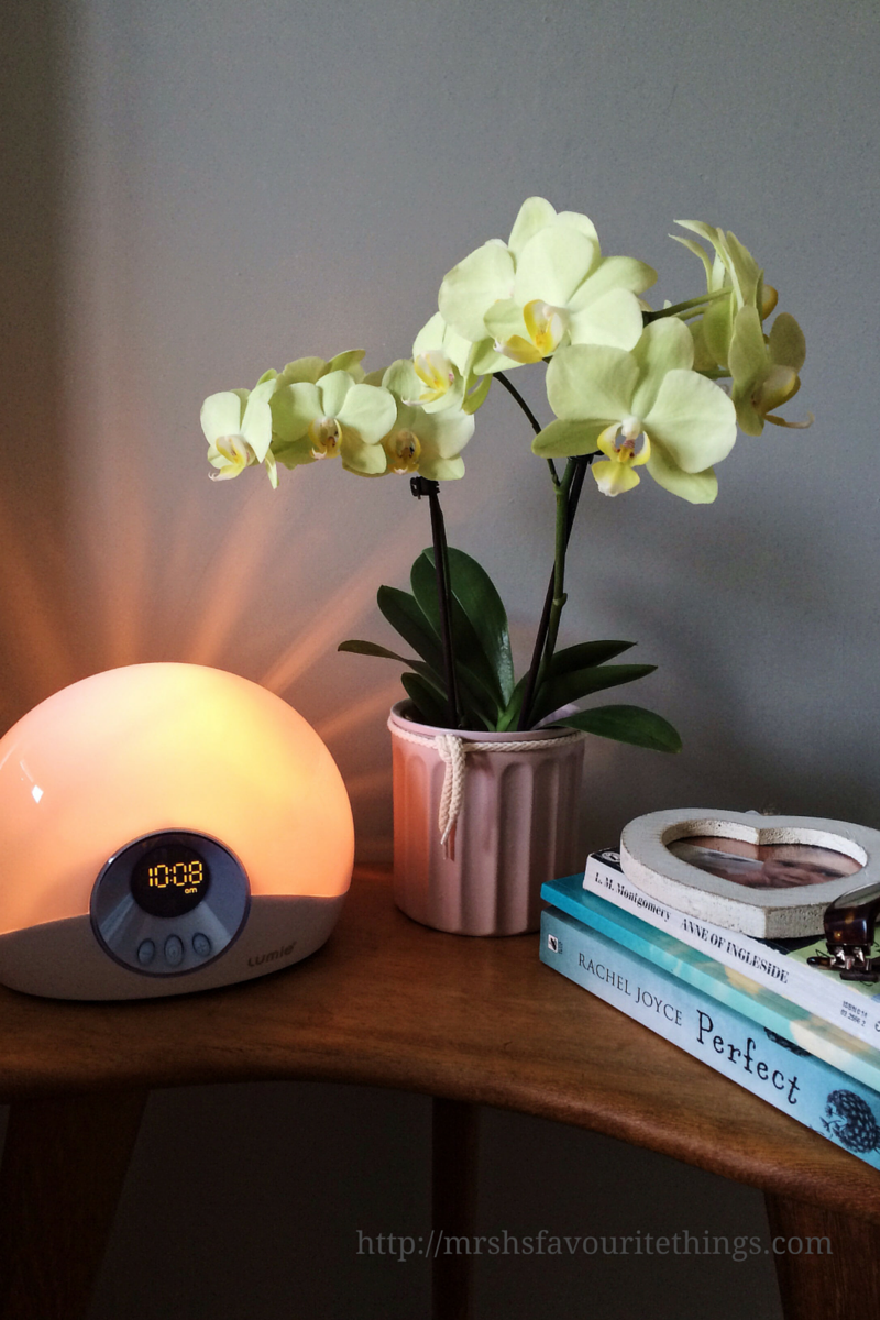 A Lumie Bodyclock STARTER 30 on a bedside table with an orchid and 3 books, a heart picture frame and a pair of glasses_Wake up brighter: Lumie Bodyclock STARTER 30 review_Mrs H's favourite things