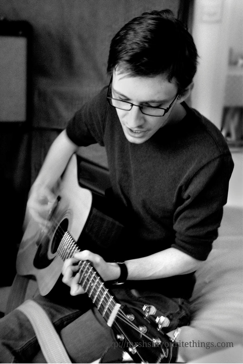 A black and white photo of a young man sitting on a bed playing an acoustic guitar _ eight pictures of happiness - Mrs H's favourite things