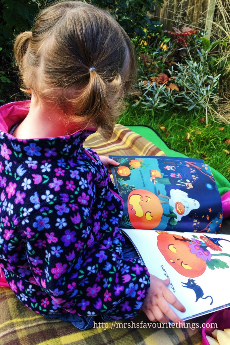 A little girl sits on a rug in her garden on an autumnal day reading Pumpkins pumpkins everywhere_ Mrs H's favourite things