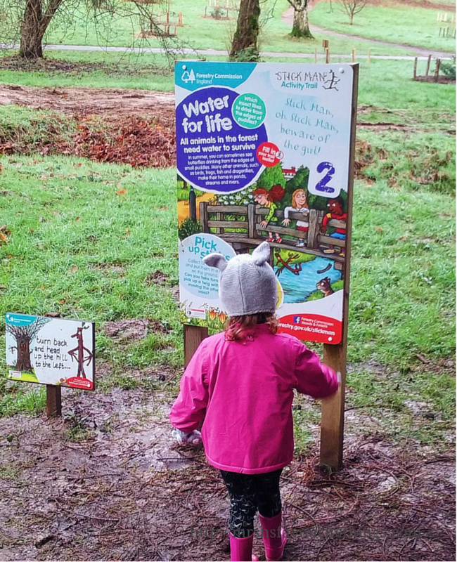 A little girl in a pink coat and rabbit hat stands in front of a sign on a Stick Man trail in a forest Days out in the winter sunshine - My Captured Moment_Mrs H's favourite things