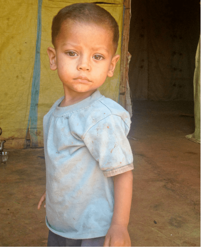 A little Syrian bo.y, aged two or three, stares sadly at the camera. He is wearing filthy clothes and stands in front of a make-shift tent in a refugee camp_From a Mother to Another - the JoJo Maman Bébé charity campaign _ Mrs H's favourite things