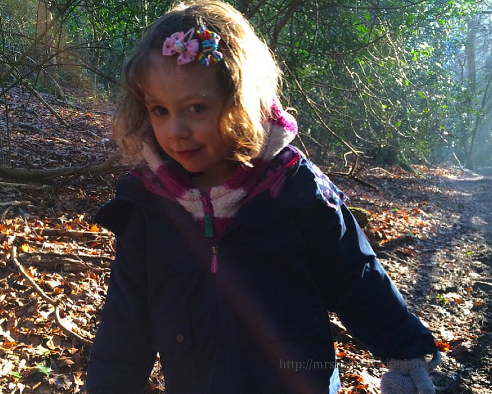 A beautiful little girl with brown curly hair stands in a sun spot in a lush wood_Because I'm happy_December 2015 and January 2016_Mrs H's favourite things