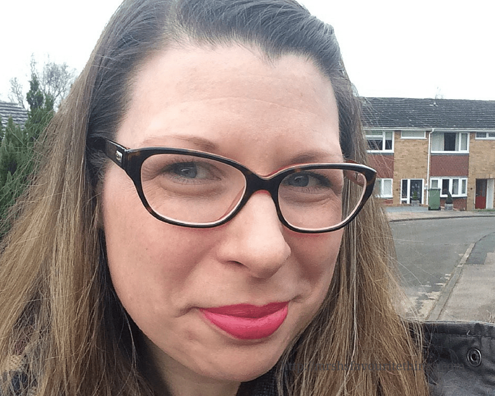 A woman with long brown hair and glasses smiles cheekily into the camera, she is wearing bright lipstick_Because I'm happy_December 2015 and January 2016_Mrs H's favourite things