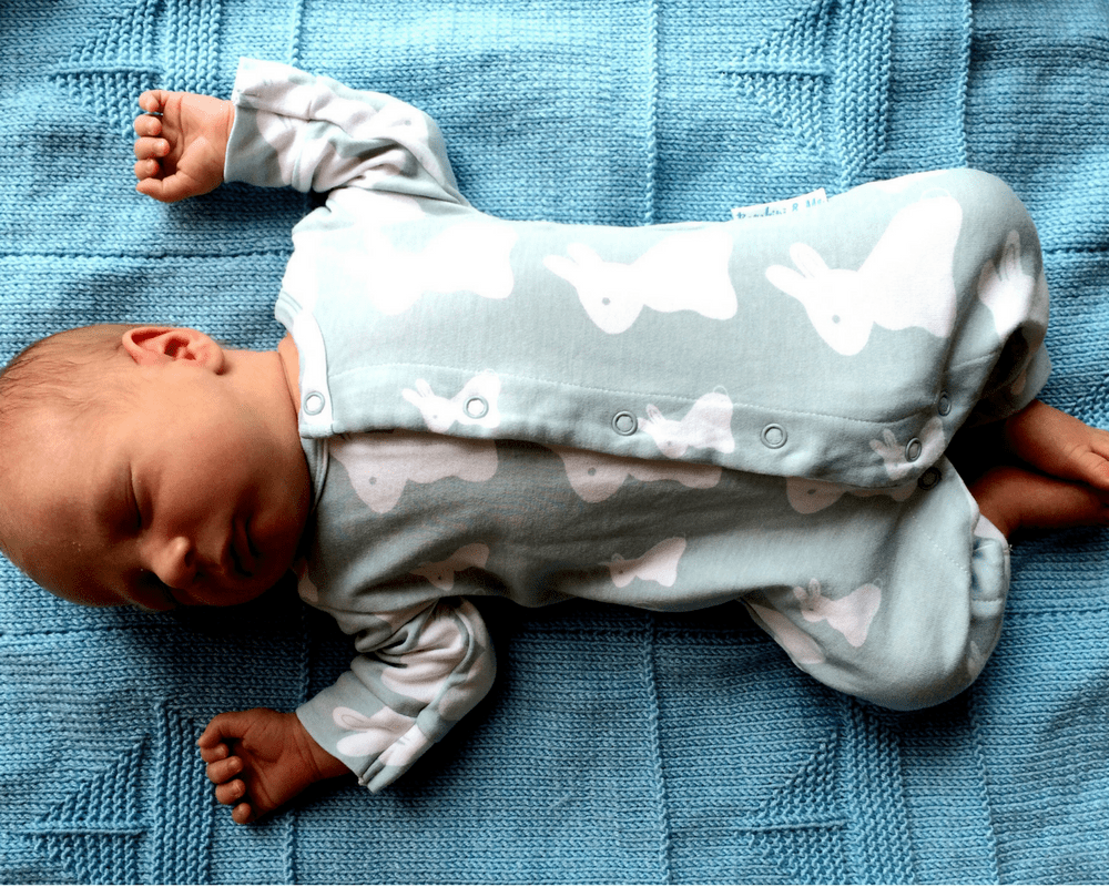 New born baby boy lying on a blue knitted blanket wearing a gorgeous crystal blue bamboo bunny romper suit from the company Bambini & Me _ Bambini & Me Giveaway