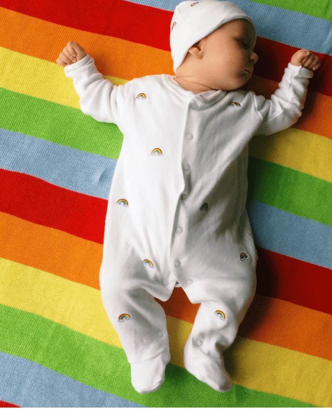 A gorgeous baby boy asleep on a brightly coloured rainbow blanket - he is wearing a Jojo Maman Bebe sleepsuit and matching hat - they are white and covered in tiny embroidered rainbows - Little Mister H at two months old - Mrs H's favourite things