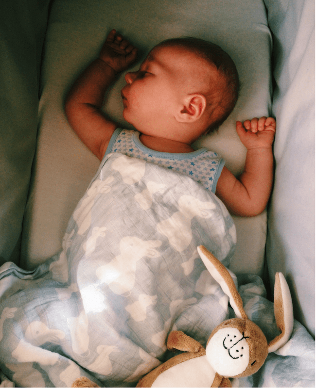 A gorgeous young baby boy lies asleep in his cot - he is covered in a bunny bamboo swaddle by the company Bambini and Me and has a small toy hare by the foot of his cot - Bambini & Me Giveaway- Mrs H's favourite things