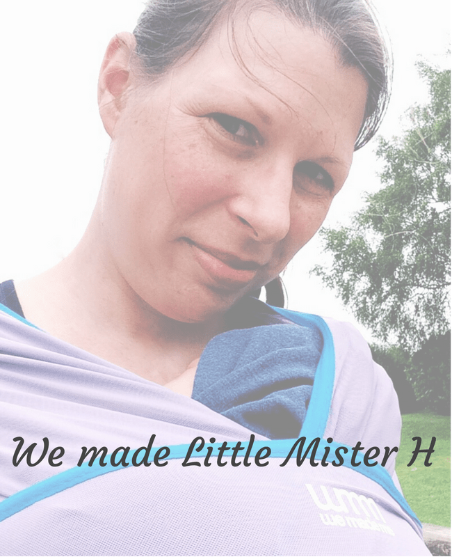 "A faded photograph of a lady with brown hair standing in a park and wearing her snoozing baby in the Wuti Wrap from the brand We Made Me - includes the blog post title ""We made Little Mister H"" - Mrs H's favourite things"
